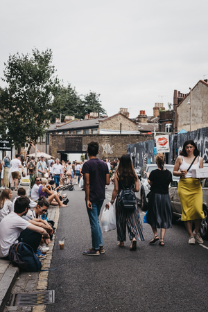 People sitting on the ground on Erza Street, relaxing after visiting Columbia Road Flower Market, a street market in East London that is open every Sunday. Editorial