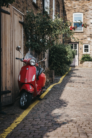 London, UK - July 17, 2018: Red Vespa motorbike parked by a house in Dunworth Mews, Notting Hill. Houses in mews are one of the most luxurious and desirable in London. Editorial