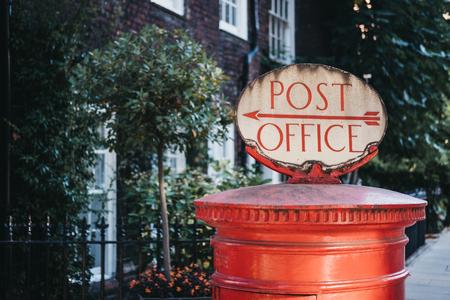 Casella postale rossa con un segno direzionale retrò ufficio postale sulla parte superiore a Londra, Regno Unito. Archivio Fotografico
