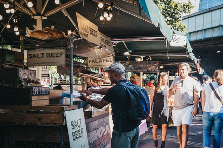 London, UK - September 17, 2018: Man buying salt beef sandwich from Nana Fanny's market stand in Borough Market, one of the largest and oldest food markets in London.