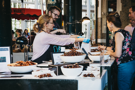 London, UK - September 17, 2018: People buying nuts at a market stall in Borough Market, one of the largest and oldest food markets in London, UK.