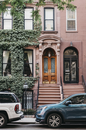 New York, USA - May 30, 2018: Facade of a typical New York house with a stoop, cars park outside. Stoops wereoriginally brought to the Hudson Valley of New York by settlers from the Netherlands. Editorial
