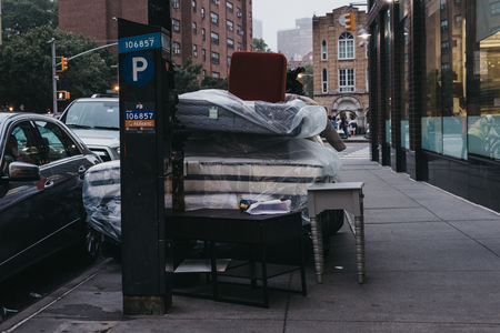 New York, USA - May 30, 2018: Furniture and mattresses dumped outside on a street in Manhattan, New York, USA. The city generates more than 11,000 tons of residential garbage daily.