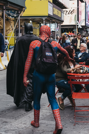 New York, USA - May 28, 2018: People dressed in Batman and Spiderman costumes walk through Times Square, a major commercial and entertainment centre and neighbourhood in Midtown Manhattan, New York. Editorial