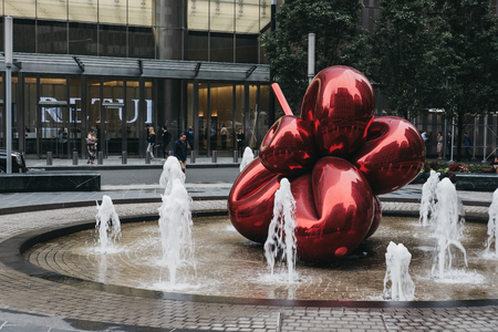 New York - May 31, 2018: Red Balloon Flower by Jeff Koons at 7 World Trade Center, New York, across from where the Twin Towers stood. The Flower is an homage to 9/11 survivors. Standard-Bild - 114644334