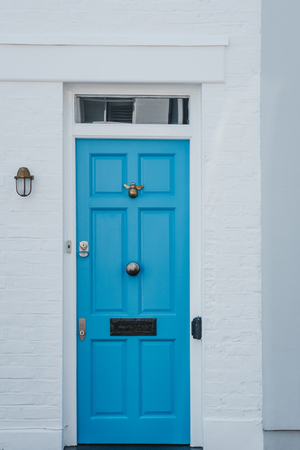 Traditional colourful bright blue door on a house in London, UK.
