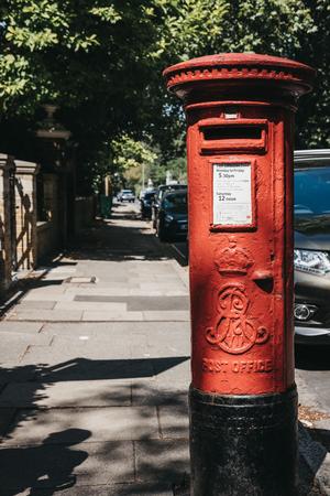 Londra, Regno Unito - 1° agosto 2018: Postbox rosso iconico appartenente a Royal Mail su una strada a Londra. Royal Mail è una società di servizi postali e corrieri del Regno Unito, fondata originariamente nel 1516.