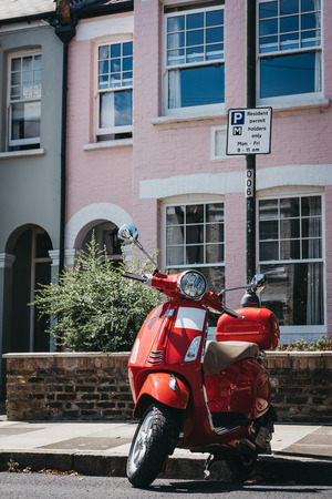 London, UK - August 1, 2018: Red Vespa motorbike parked by a house in Barnes, London. Vespa is a famous Italian brand of scooter manufactured by Piaggio.