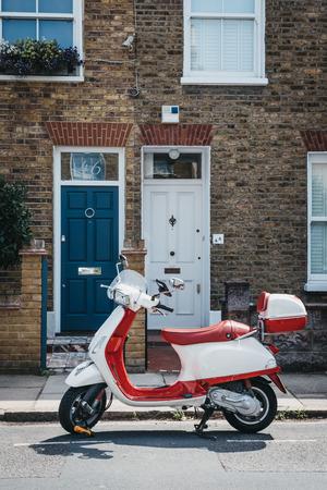 Londres, Reino Unido - 1 de agosto de 2018: Moto Vespa roja y blanca estacionada junto a una casa en Barnes, Londres. Vespa es una famosa marca italiana de scooter fabricada por Piaggio.