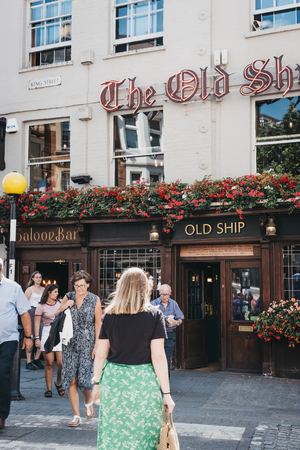 London, UK - August 1, 2018. People crossing the road in front of The Old Ship pub in Richmond, a suburban town in south-west London famous for a large number of parks and open spaces. Editorial