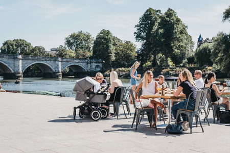 London, UK - August 1, 2018. Two people sitting and relaxing at outdoor tables by the River Thames in Richmond, a suburban town in south-west London famous for a large number of parks and open spaces.