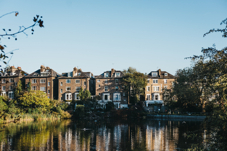 London, UK - October 27, 2018: Row of semi-detached houses in Hampstead, facing a pond in Hampstead Heath. Hampstead Heath covers 320 hectares one of Londons most popular open spaces. Editorial