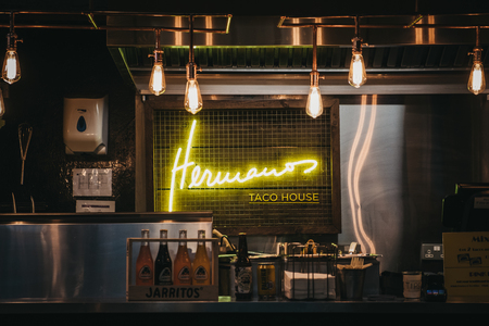 London, UK - November 2, 2018: Hermanos Taco House stand in Mercato Metropolitano, the first sustainable community market in London focused on revitalising the area and protecting environment. Editoriali
