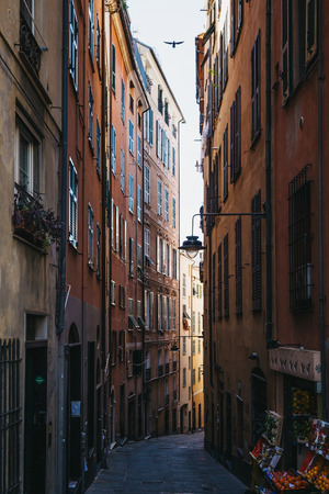 Genoa, Italy - October 30, 2016: View of a narrow street of Genoa, one of Europe's largest cities on the Mediterranean sea and the largest seaport in Italy. Editorial