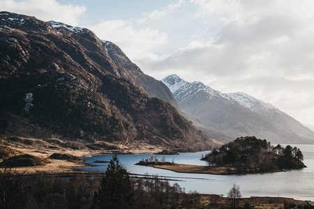 View of the Loch Shiel and Scottish landscape near Glenfinnan, Inverness-shire, Scotland, on a cold spring sunny day. Banque d'images - 114669524