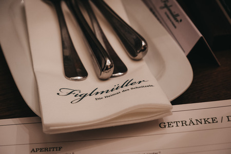 """Vienna, Austria - Novermber 24, 2018: Cutlery on the table in Figlmuller on Wollzeile restaurant in Vienna. Opened in 1905, it is often referred to as the """"Home of the Schnitzel"""". Editorial"""