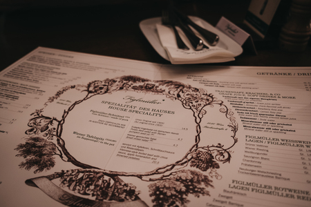 """Vienna, Austria - Novermber 24, 2018: Menu on the table at Figlmuller on Wollzeile restaurant in Vienna. Opened in 1905, it is often referred to as the """"Home of the Schnitzel""""."""
