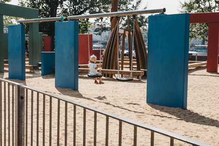 Unidentifiable child sitting alone on a swing in a playground, rear view.