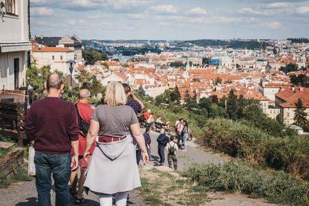 Prague, Czech Republic - August 26, 2018: Group of tourists walking down a path overlooking rooftops of Prague's Lesser Town, one of the city's most historic regions.