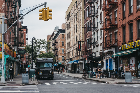 New York, USA - May 29, 2018: People and cars on a street in Lower East Side, New York, USA.  New York is one of the most visited cities in the world.