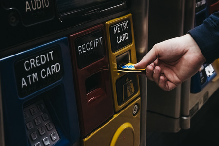 New York, USA - May 29, 2018: Male hand puts Metro Card into a top up machine at a subway station in New York. A MetroCard is used as a ticket and can operate in two modes: Regular and Unlimited Ride.