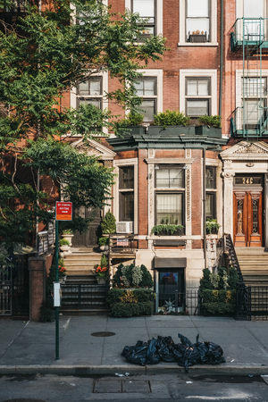 New York, USA - May 30, 2018: Facade of a typical New York house with a stoop, rubbish in black bins in front of it. The city generates more than 11,000 tons of residential garbage daily.