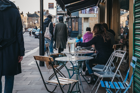 London, UK - February 03, 2019: People sitting at an outdoor table of a cafe on Broadway Market, a shopping street in the heart of Hackney, East London, UK.