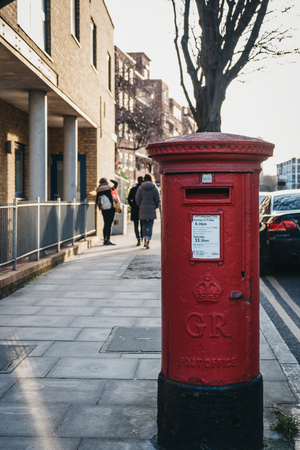 London, UK - February 3, 2019: Red postbox belonging to Royal Mail on a street in London. Royal Mail is a postal service and courier company in the United Kingdom, originally established in 1516.