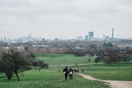 London, UK - February 16, 2019: People walking on Primrose Hill, 65 m hill on the northern side of Regents Park, London, that has also given name to the surrounding district. City on the back. Editorial