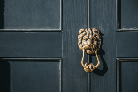 Close up of a lion's head door knocker on a black door of a house.