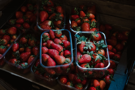 Top view of fresh strawberries on sale, portioned in plastic boxes, on top of a wooden table