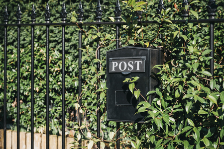 Close up of a black post box outside a house on a fence against greenery on a sunny day.