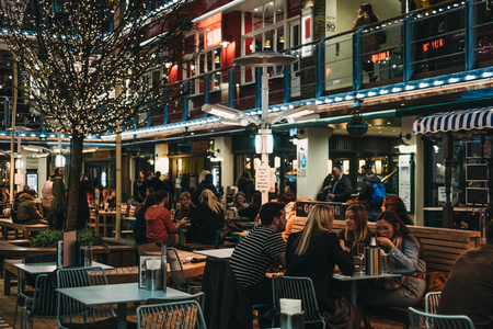 London, UK - March 6, 2019: People sitting at the outdoor tables of Kingly Court, a three-storey alfresco food and dining courtyard in the heart of London's West End. Redactioneel