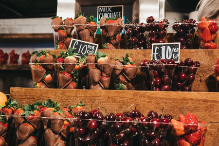 Cups of fresh strawberries, cherries and  strawberries dipped in milk chocolate on sale, portioned in plastic cups, on top of a wooden shelves. Reklamní fotografie