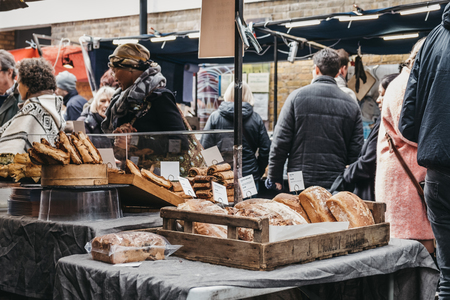 London, UK - March 16. 2019: People buying fresh bread and pastries from a market stall at Greenwich Market, Londons only market set within a World Heritage Site.