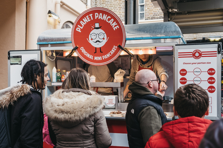 London, UK - March 16. 2019: People buying mini pancakes from a Planet Pancake stand at Greenwich Market, Londons only market set within a World Heritage Site.