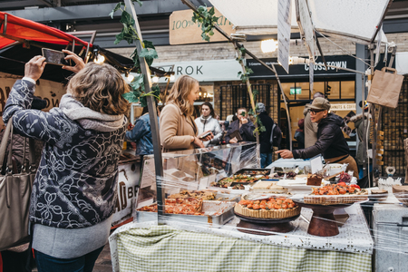 London, UK - March 16. 2019: Woman buying cakes from a market stall at Greenwich Market, Londons only market set within a World Heritage Site.
