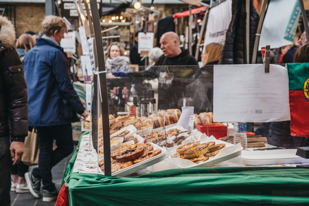 London, UK - March 16. 2019: Man buying cakes and pies from a market stall at Greenwich Market, Londons only market set within a World Heritage Site. Selective focus on the foreground.