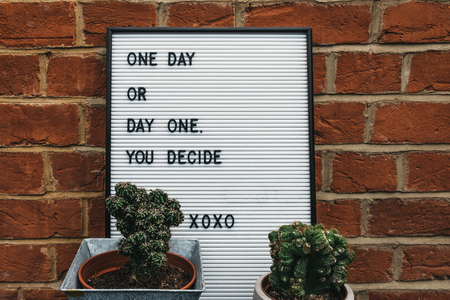 One day or day one motivational quote on a white board against brick wall.