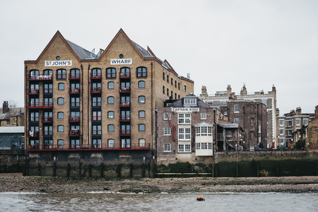 London, UK - March 16, 2019: View of St. Johns Wharf, a warehouse converted into residential flat, from River Thames, London. Real estate in London is amongst the most expensive in the world. Redakční
