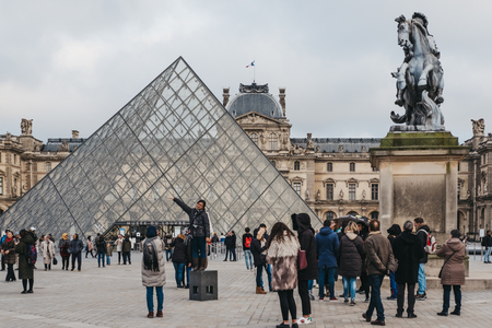 Paris, France - January 27, 2018: Tourists taking pictures in front on the Louvre, the worlds largest art museum and a historic monument in Paris, France.