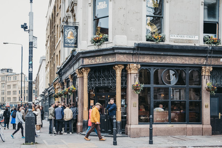 London, UK - April 6, 2019: People standing and drinking outside The Ten Bells pub in Shoreditch, East London, pub famous for its supposed association with two victims of Jack the Ripper. Editorial