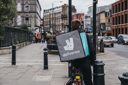 London, UK - April 6, 2019: Deliveroo delivery driver on a street in East London. Deliveroo is a British-born company that enables food to be delivered from restaurants that do not offer delivery.