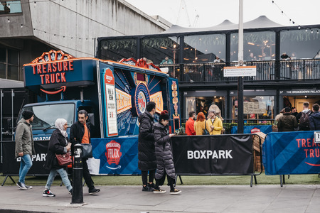 London, UK - April 6, 2019: People walking past Amazon truck parked at BOXPARK Shoreditch, shipping container pop-up mall for independent and fashion and lifestyle stores and cafes. Redactioneel