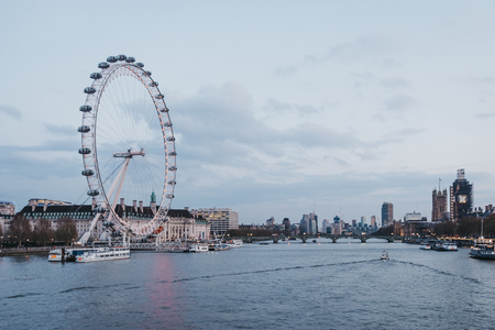London, UK - April 13, 2019: View of London Eye, city skyline and landmarks from Millennium Bridge. London is one of the most visited cities in the world.