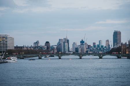 London, UK - April 13, 2019: View of London skyline and landmarks from Millennium Bridge during blue hour. London is one of the most visited cities in the world. Editorial