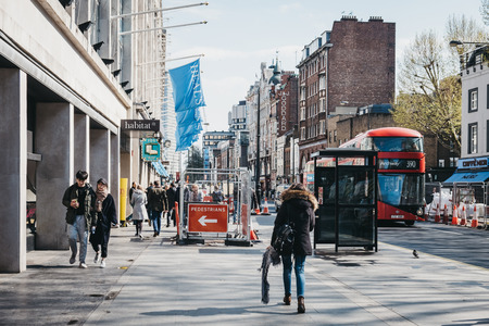 London, UK - April 13, 2019: People walking on Tottenham Court Road, London, on a sunny spring day. Historically a market street, nowadays it is well known for selling electronics and white goods.