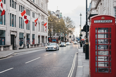 London, UK - April 13, 2019: Cars driving past Canadian Flags on Canada House in Charing Cross, London. The building houses offices of the High Commission of Canada in the United Kingdom since 1925.