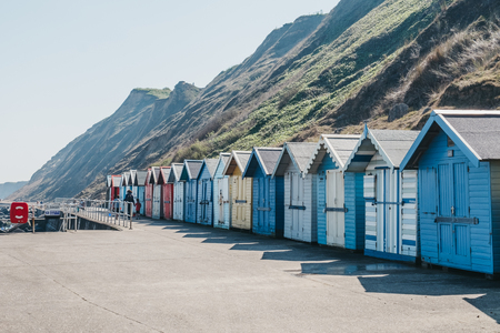Sheringham, UK - April 21, 2019: People walking by colourful beach huts by the sea in Sheringham on a sunny day. Sheringham is an English seaside town within the county of Norfolk, UK.