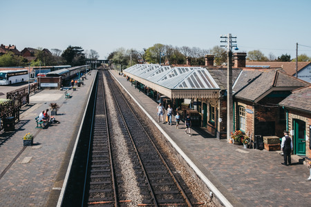 Sheringham, UK - April 21, 2019: View from above of people walking on a platform of Sheringham train station on a sunny day. Sheringham is an English seaside town within the county of Norfolk, UK. Редакционное